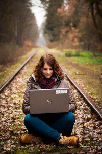 Nicole sitzt mit Laptop auf den Gleisen